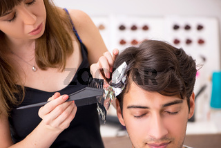 The young attracrive man visiting female barber