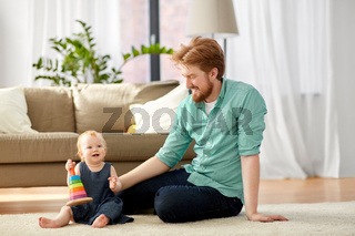 father playing with little baby daughter at home