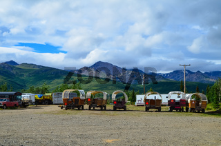 Wells Fargo horse wagons with mountains in the background and cloudy sky above. Healy, Alaska, United States