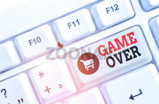 Text sign showing Game Over. Conceptual photo A situation in a particular sport that reach his finals or ending White pc keyboard with empty note paper above white background key copy space.