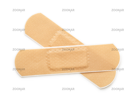 Top view of two beige adhesive bandages