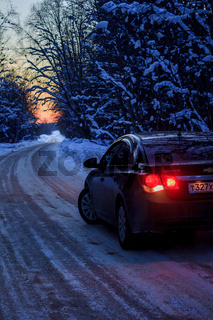 Car on the winter road in the evening. Night road. Road outside the city. Car out of town in the winter. Russia, Leningrad region, March 1, 2018