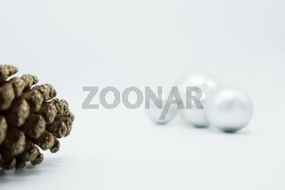 White Christmas balls on white background with pine cone.