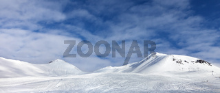 Ski slope with print from skis, snowboards and foot, snowy mountain