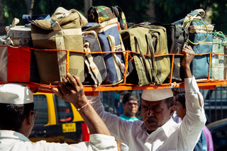 Indian man loads on a basket full of Dabbawala hot lunches on to his head