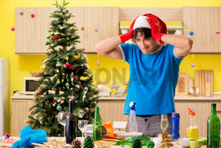 The young man cleaning kitchen after christmas party