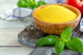 Uncooked Italian polenta in a wooden bowl.