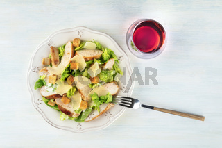 Chicken Caesar salad, shot from the top with a glass of wine and a place for text