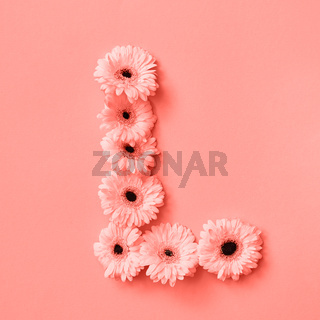 Letter L made from flowers gerbera on a color background of the year 2019 Living Coral Pantone. Part of the word LOVE. Top view. Place for text.