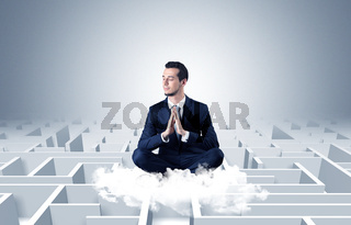 Businessman meditates on a cloud with maze concept