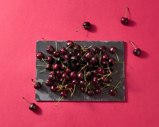 Delicious sweet cherry on a black stone board on red paper background with place for text. Flat lay.