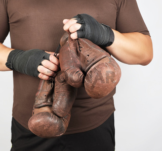 adult man in brown sport uniform holds a pair of brown vintage casual boxing gloves