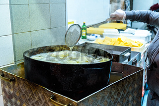 Pot with boiling oil to prepare the typical Polenta Gialla, boiled corn flour, traditional from Italy and countries of South America.
