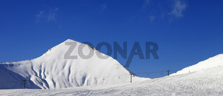 Ski slope with ropeway at sunny winter day