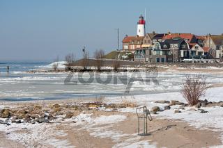 Dutch lighthouse in wintertime near a frozen sea