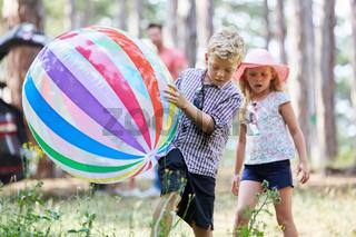 Geschwister spielen mit einem bunten Ball