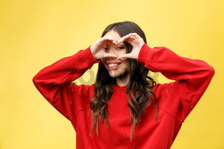 portrait smiling young woman making heart sign with hands.