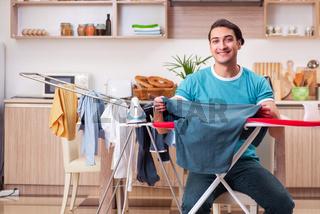 Young man husband doing clothing ironing at home