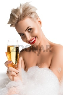 Beautiful blonde in bath with a glass of champagne