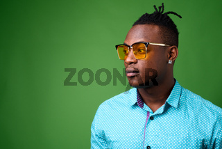 Young handsome African man from Kenya against green background