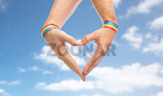 male hands with gay pride wristbands showing heart