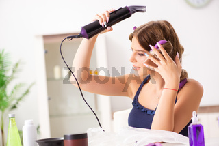 The young woman with hair curlers at barbershop