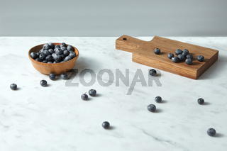 Summer organic natural sweet blueberries in a wooden plate, board on a white with copy space.