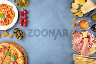 Italian food. Pizza, pasta, cheese, hams, wine and capers, shot from above with a place for text, a flat lay composition