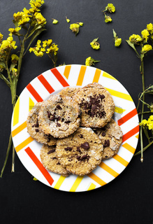 Oatmeal cookies with chocolate on a plate with bright yellow flowers