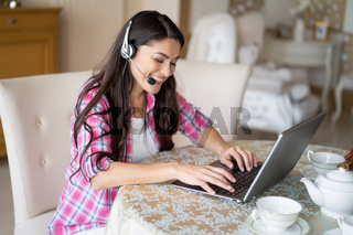 Beautiful woman works at her laptop wearing headsets