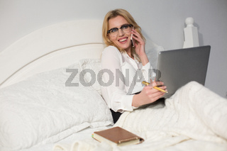 Businesswoman sitting in bed, using laptop