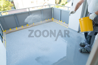 construction worker renovates balcony floor and spreads chip floor covering on resin and glue coating before applying water sealant