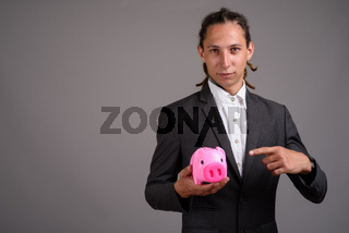 Young businessman with dreadlocks against gray background