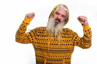 Studio shot of senior bearded man wearing hoodie while flexing b