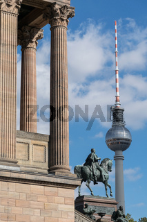BERLIN, GERMANY - SEPTEMBER 26, 2018: Bright and contrasting view of the antique architecture of the Alte national galerie and the statue of it's entrance and the modern TV tower in Berlin