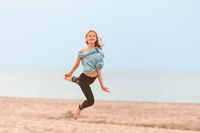 Young girl jumping in the air on the beach