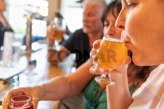 Female Sipping Glass of Micro Brew Beer At Bar With Friends