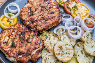 Chopped chicken cutlet with grilled vegetables lie on a plate. Grilled poultry and vegetables. Beautiful food. Food layout.